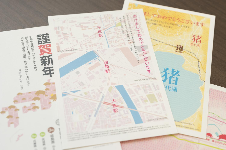 長縄さんデザインの歴代年賀状。今年は新元号に変わる年ということで、「大正」駅、「昭和」駅、「平成」駅付近の地図がデザインされている
